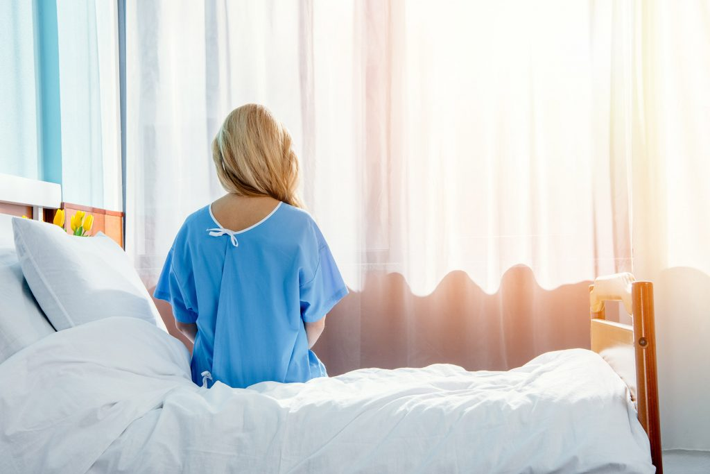 Woman Sitting on Edge of Bed in Hospital, Worried About IVC Filter